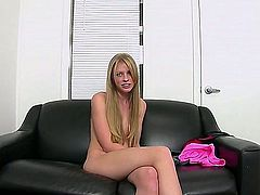 Cute long haired blonde girl Avril Hall is naked on the couch with legs together. Shy naked girl hides her tits and pussy during interview. Would you like to see her pink snatch!