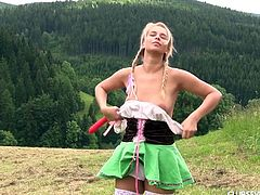 Young blonde in stockings and short skirt Nikki Dream is playing with dildo in the meadow