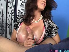 Bigtitted milf tugging hard cock and stroking it between her boobs